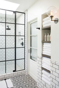 White and black bathroom boasts an alcove filled with shelves holding towels alongside a white and black floor in Cement Tile Shop Bordeaux Tiles.