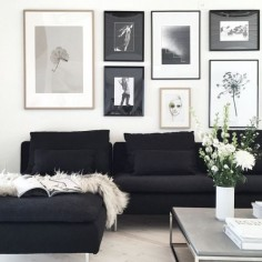 black chaise lounge, grey stone coffee table and a wall of frames